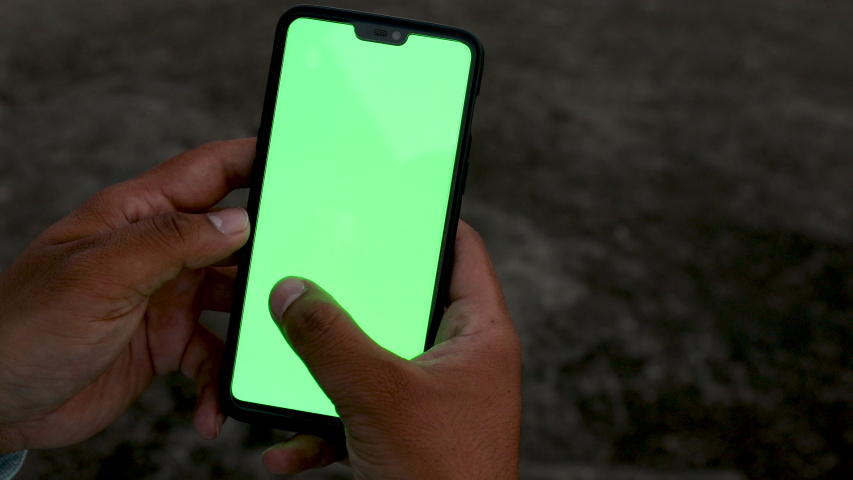 Man holding and using a smartphone with green screen | Shutterstock HD Video #1039008377
