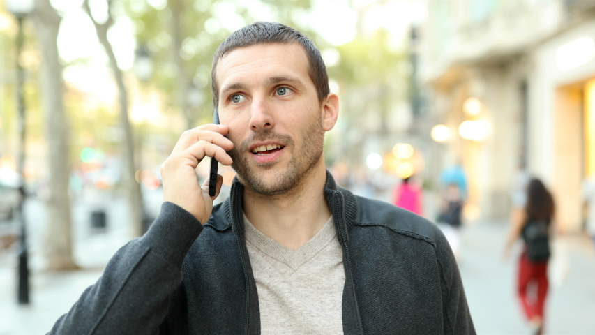 Front view of a serious adult man talking on mobile phone walking towards camera in the street | Shutterstock HD Video #1039011677