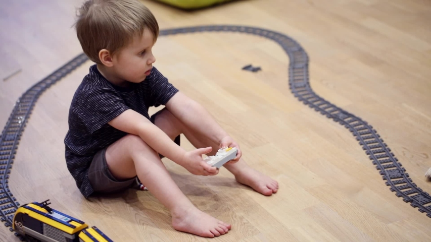 Four years old sad child boy play with radio train, constructed toy railroad at home. Toddler boy playing. Educational toys for preschool child, indoor playground, lifestyle concept   Shutterstock HD Video #1039012037