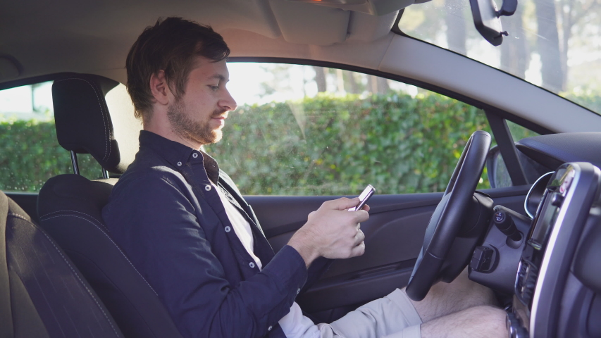 Stylish young man using smart phone in the car. | Shutterstock HD Video #1039029887
