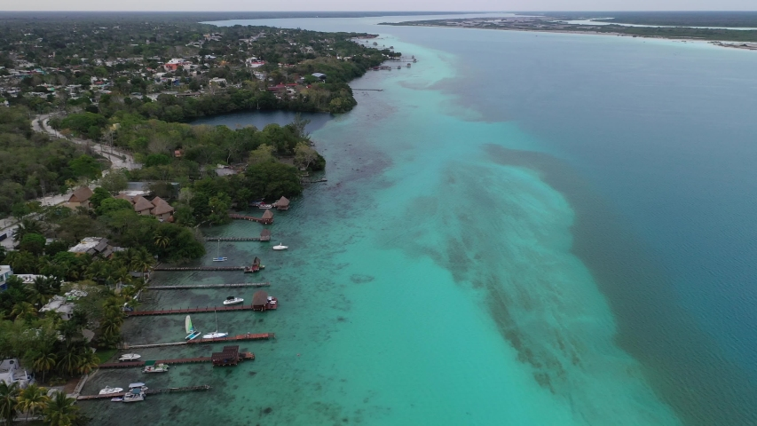 Aerial view of lined up boat docks in tropical water. Lagoon of Seven Colors. Amazing tourist travel destination. Bacalar, Mexico. | Shutterstock HD Video #1039033697