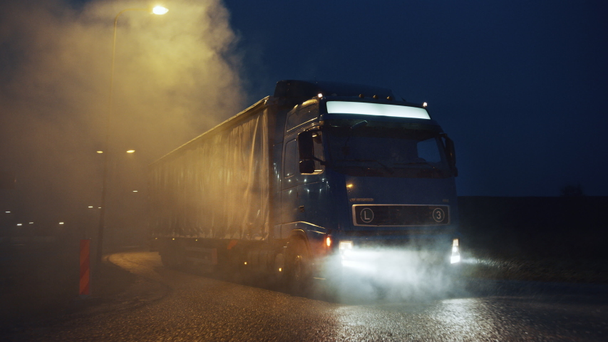 Blue Long Haul Semi-Truck with Cargo Trailer Full of Goods Travels At Night , Turning on the Freeway Road, Driving Across Continent Through Rain, Fog, Snow. Industrial Warehouses Area. Front Following | Shutterstock HD Video #1039037177