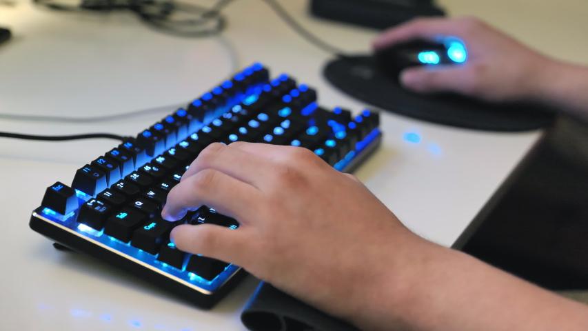 Teenagers hands typing on gaming keyboard. Keyboard keys are backlit.   Shutterstock HD Video #1039162367