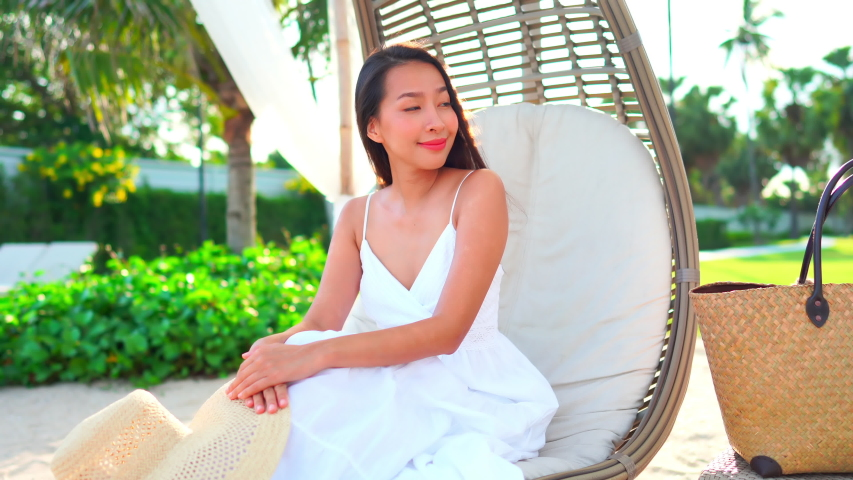 Asian woman in white summer dress sitting outside in a wooden swing at a tropical island luxury resort. Pretty lady with large beach bag holding a fashionable hat smiles in the sunlight. | Shutterstock HD Video #1039184417