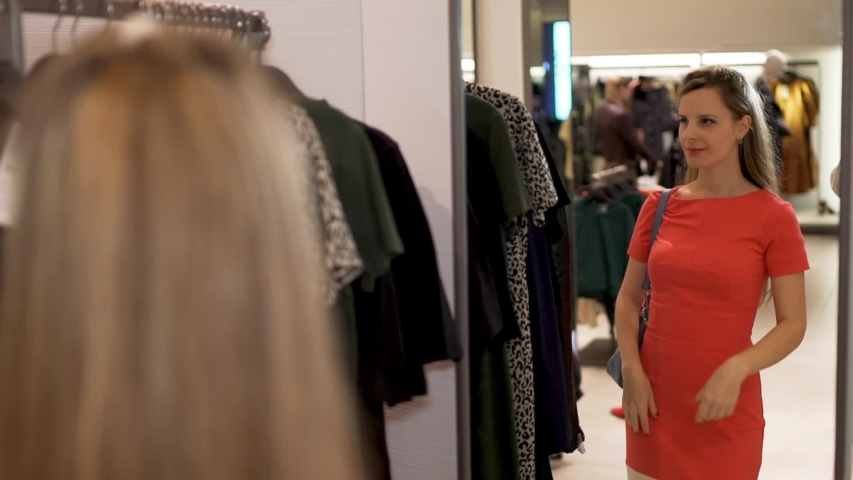 The girl-the buyer takes from a hanger of shop a fashionable black dress. A woman applies a dress to herself and looks in the mirror in a fashion boutique store in a shopping center, close-up | Shutterstock HD Video #1039187927