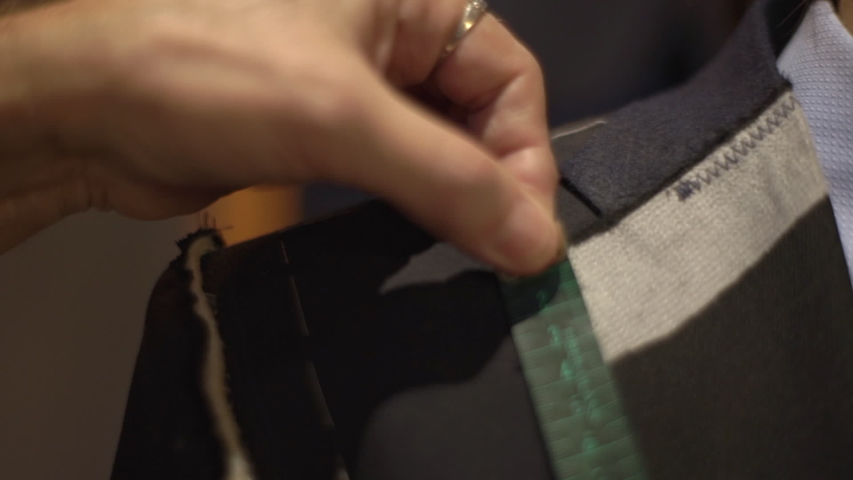 Close-up of man shoulder as tailor taking measures with measuring tape, craftsman pin sleeves and adjust handmade suit during fitting in atelier, businessman order jacket. Fashion concept | Shutterstock HD Video #1039192337