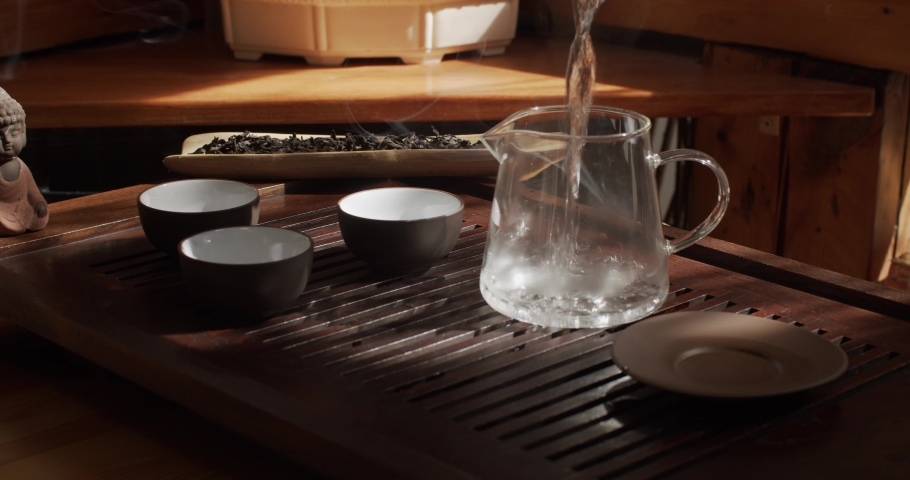 Faceless person pouring hot water into glass kettle preparing tea ceremony indoors slow motion. Male hand holding clay crockery ready to drink elite beverage natural light. Exotic eastern culture zen  | Shutterstock HD Video #1039251467