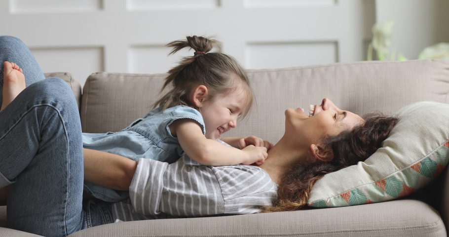 Happy carefree mother and cute small child daughter tickling laughing having fun lying on sofa and playing, smiling mum enjoying bonding cuddling hugging spending time with little funny kid at home