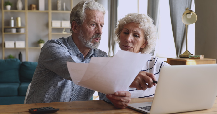 Worried senior retired couple checking calculating bills bank loan payment doing paperwork discuss unpaid debt taxes, stressed old grandparents family look at laptop upset about money problem concept