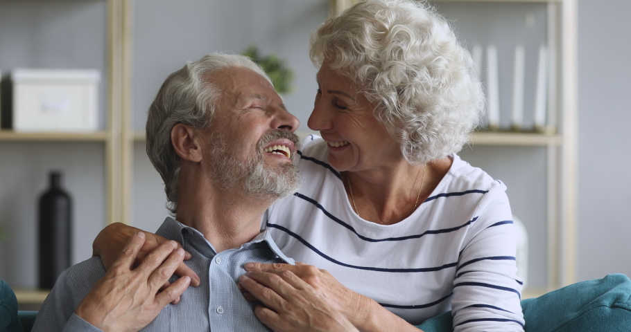 Happy loving elderly old couple grandma and grandpa embracing bonding relaxing sit on couch looking at camera, smiling senior retired family enjoy hugging on sofa in living room grandparents portrait | Shutterstock HD Video #1039337957