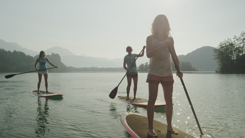 SLOW MOTION: Surfer girls SUPing on the beautiful lake towards the camera at sunrise