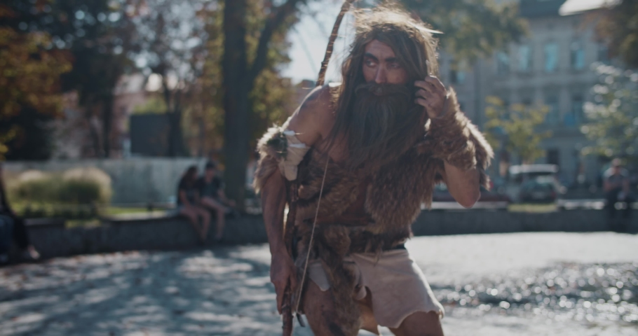 Close up caveman discoverer look around in animal fur exploring future city architecture modern civilization neanderthal barbarian aboriginal civilization curiosity earliest evolution slow motion | Shutterstock HD Video #1039519487