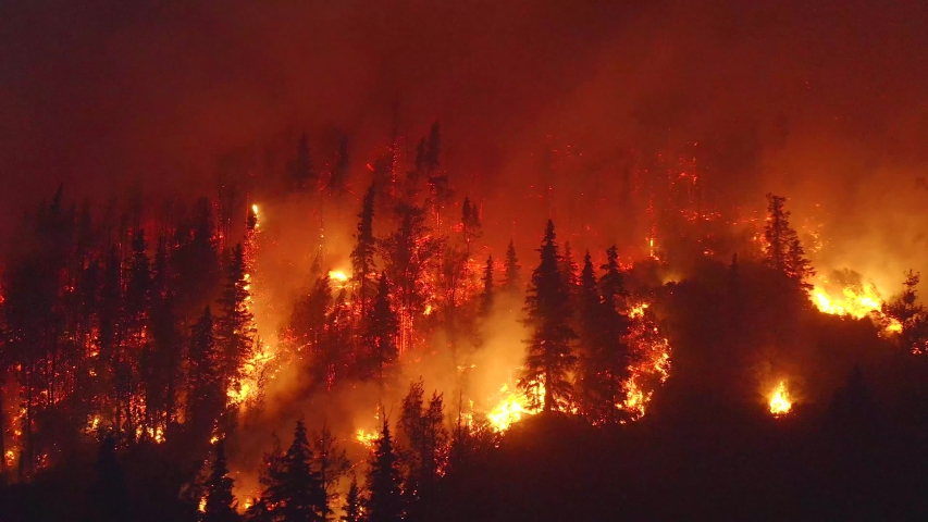 Aerial, tracking, drone shot, overlooking forest in flames, Alaskan wildfires destroying and causing air pollution, on a dark, summer night, in Alaska, USA | Shutterstock HD Video #1039559957