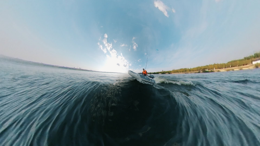 Zoom-in of a man, fisherman sailing on a motorboat | Shutterstock HD Video #1039658207
