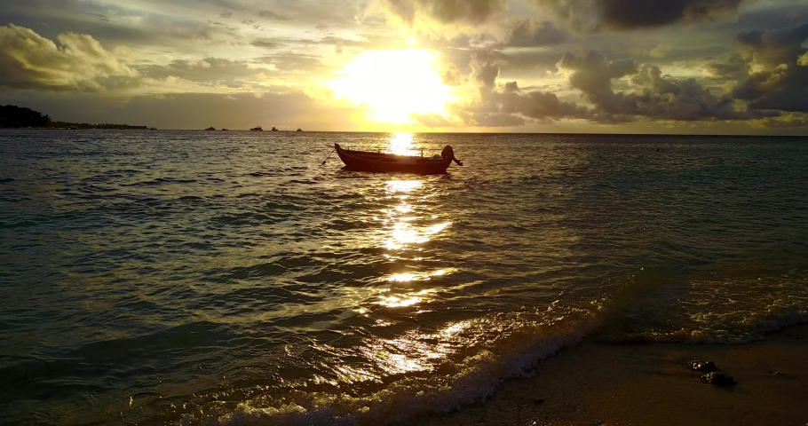 Sunset over water in Malaysia, backlit old wooden fisherman boat with waves gently breaking on the shore in the foreground | Shutterstock HD Video #1039702577