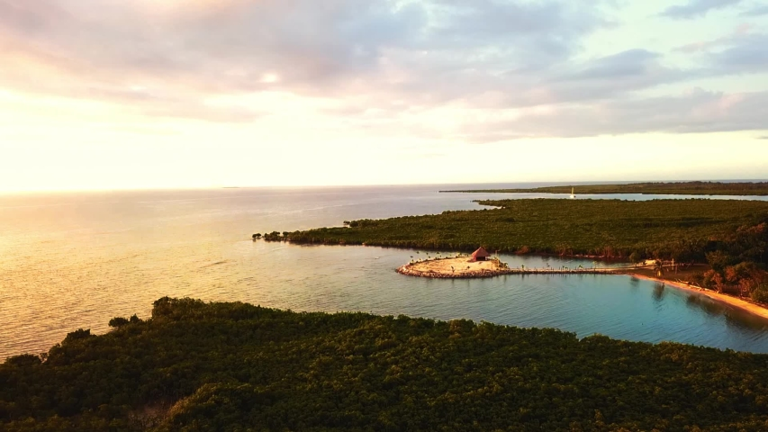 Aerial view: Flying towards small artificial island in divine sunset   Shutterstock HD Video #1039869107