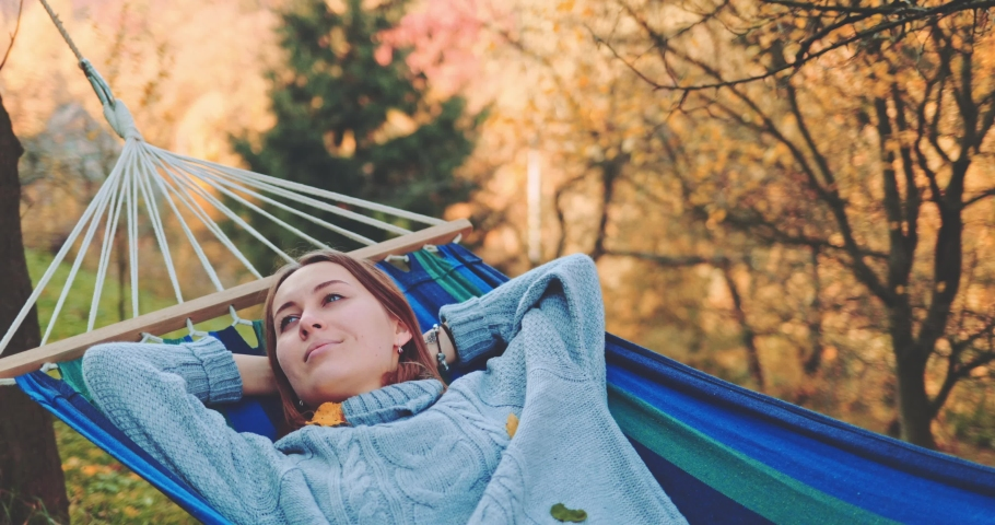 Woman Relaxes in a Hammock in Autumn. SLOW MOTION. Young woman daydreams, unwinds in a calm fall outdoor, rural country nature with colourful forest in background. Cozy morning or evening. | Shutterstock HD Video #1040004377
