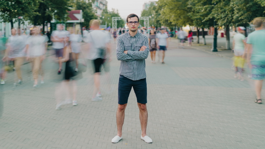 Zoom-in time lapse of attractive guy standing in city street with arms crossed while crowds of men and women are rushing around. People and modern urban life concept. #1040181077