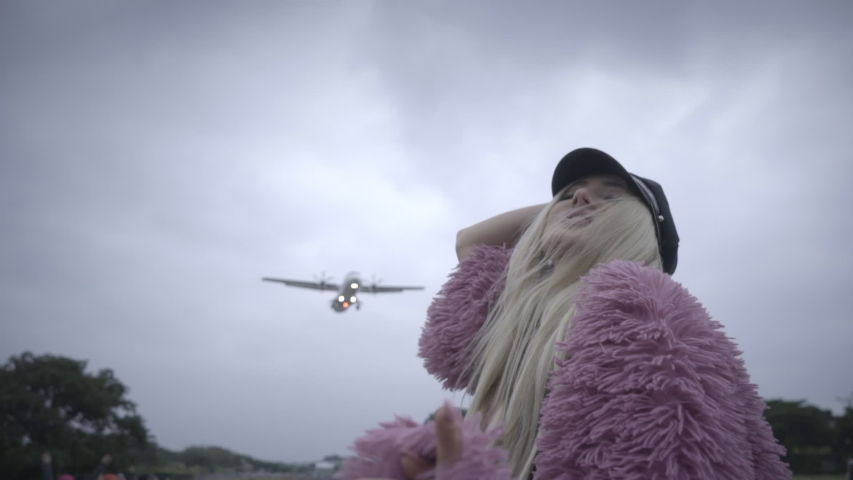 Young unusual woman with blonde hair in pink fur coat posing and dancing on background of arriving aircraft. Plane landing over happy girl near airport and runway. Travel concept. | Shutterstock HD Video #1040423087