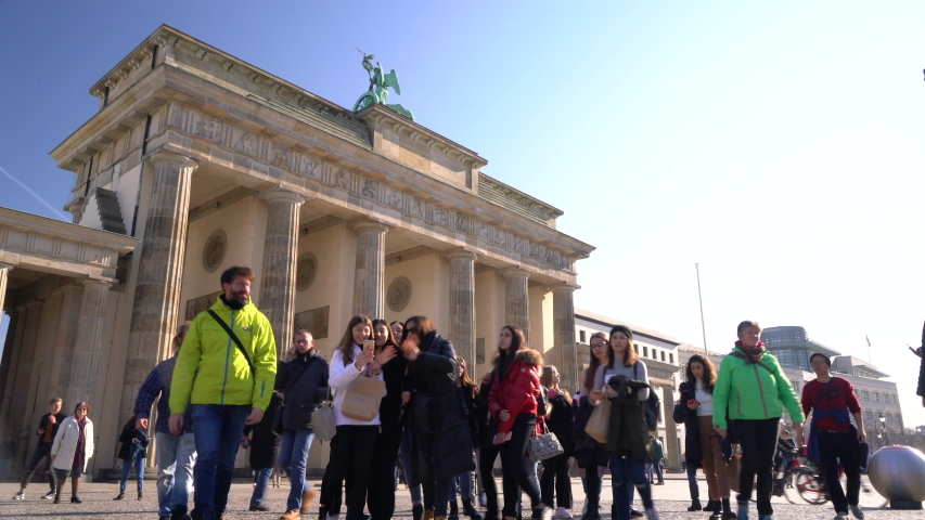 THE BRANDENBURG GATE, BERLIN, GERMANY – 18 FEBRUARY 2019, Tilt down to people, tourists and students during the day by The Brandenburg Gate, Berlin, Germany