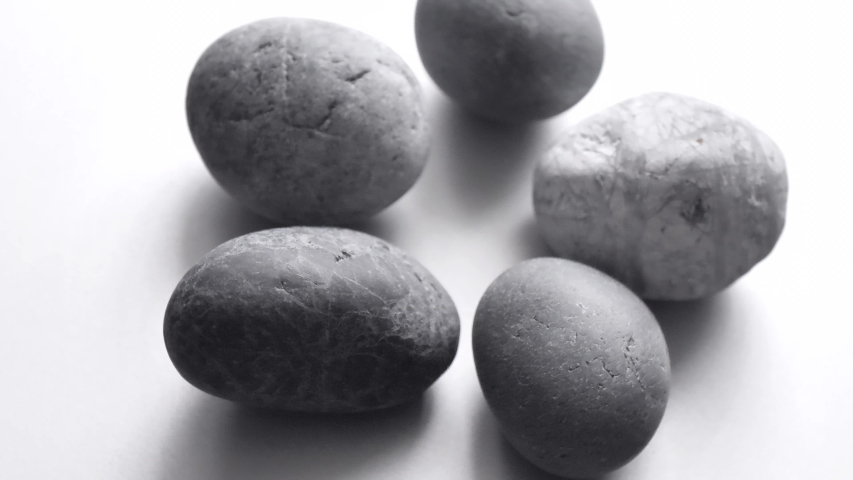 Closeup gray round stones spin on a light gray background. Ordinary plain gray pebble stones. Background for meditation and relaxation. | Shutterstock HD Video #1040459597