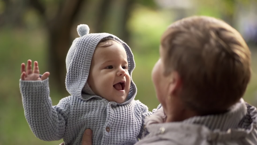 Grandmother with baby boy in autumn park having fun, smiling, playing. Grandson is happy to communicate with elderly great-grandmother   Shutterstock HD Video #1040682077