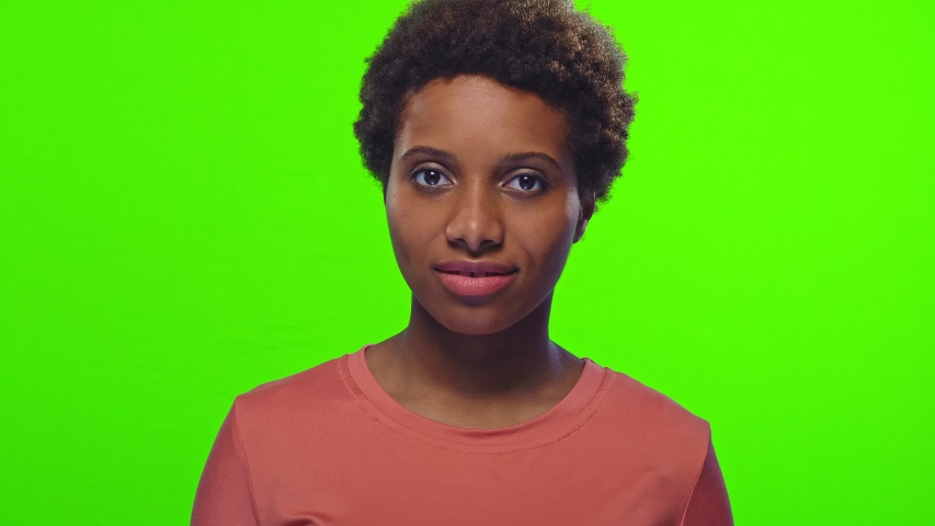 Portrait of playful funny young African American woman with glad expression, blinks eye, flirts with boyfriend, expresses good emotions, over chroma key background. Hey, guy look at me | Shutterstock HD Video #1040707517