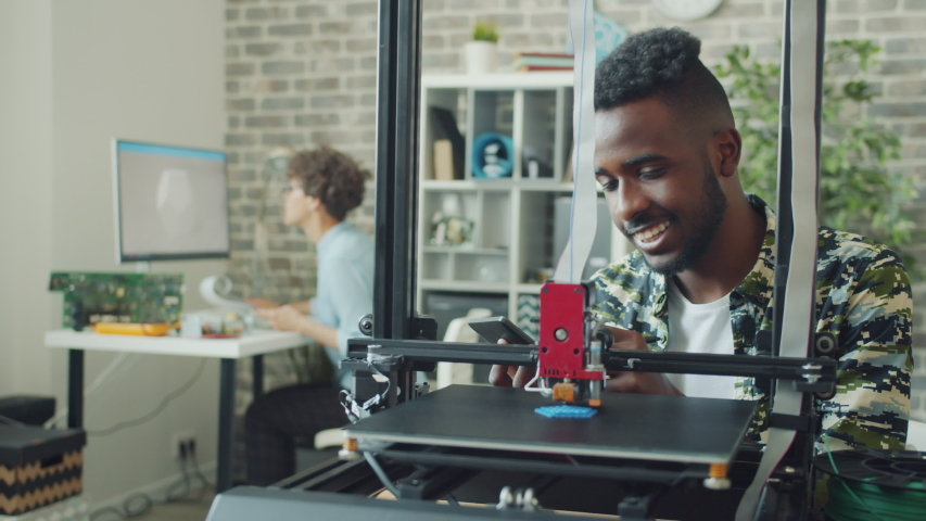 Afro-American man worker is using tablet looking at 3d printer manufacting model in office. Innovation, contemporary business and electronics concept.