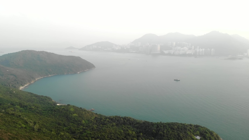 Aerial view. The emerald-colored sea separates the island of Lamma and Hong Kong. Hilly area with lots of greenery. China   Shutterstock HD Video #1040818937