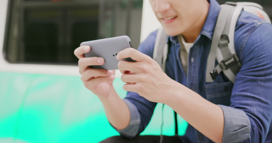 Close up of asian young man play game with 5g smartphone on the mrt or train | Shutterstock HD Video #1040827277