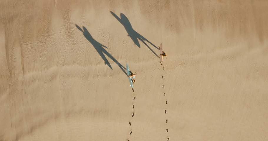 Aerial view of two young adventurous friends going surfing together at sunrise, fun couple walking on the beach with surfboards with artsy shadows | Shutterstock HD Video #1040876567