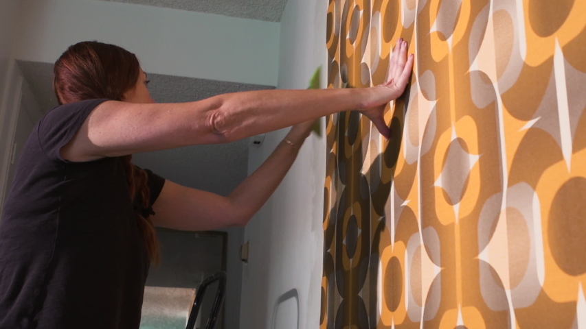 Real woman improving, renovating and decorating her home by hanging 1970's retro wallpaper | Shutterstock HD Video #1040883197