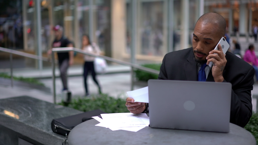 Serious male finance director making international call with business partner via application on cellular using roaming connection while working remotely outdoors with laptop device for accounting | Shutterstock HD Video #1040953847