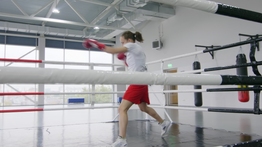 View through ropes of ring of professional female boxer in sportswear and gloves practicing punches while exercising in gym with panoramic windows | Shutterstock HD Video #1041001457