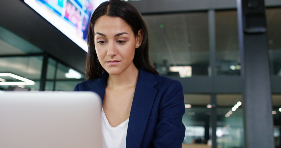 4K Businesswoman working in office with screen displaying business & news report | Shutterstock HD Video #1041089347