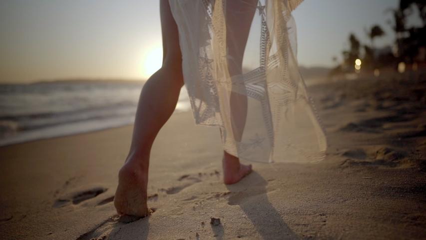 Woman walks along beach barefoot wearing light flowing dress blowing in the wind | Shutterstock HD Video #1041245017