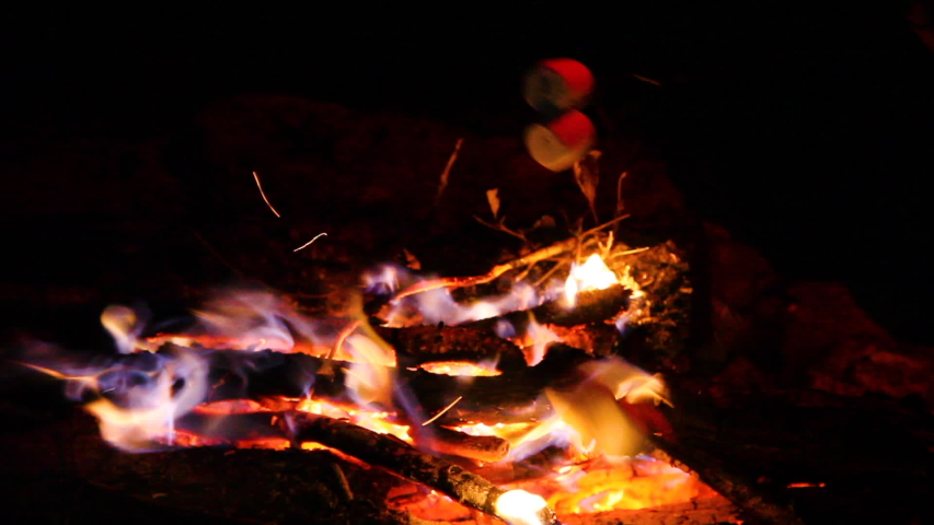 Roasting marshmallows over an open campfire. They are on metal skewers and being turned so they do not burn. Heat waves skew the light. Two marshmallows on each roasting stick. Colorful fire blue red.   Shutterstock HD Video #1041448987