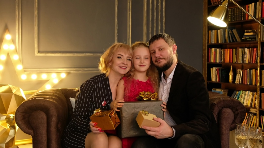 Father, mother and daughter to give mutually christmas gifts (presents). Family celebrates the new year holiday at home.  | Shutterstock HD Video #1041456877