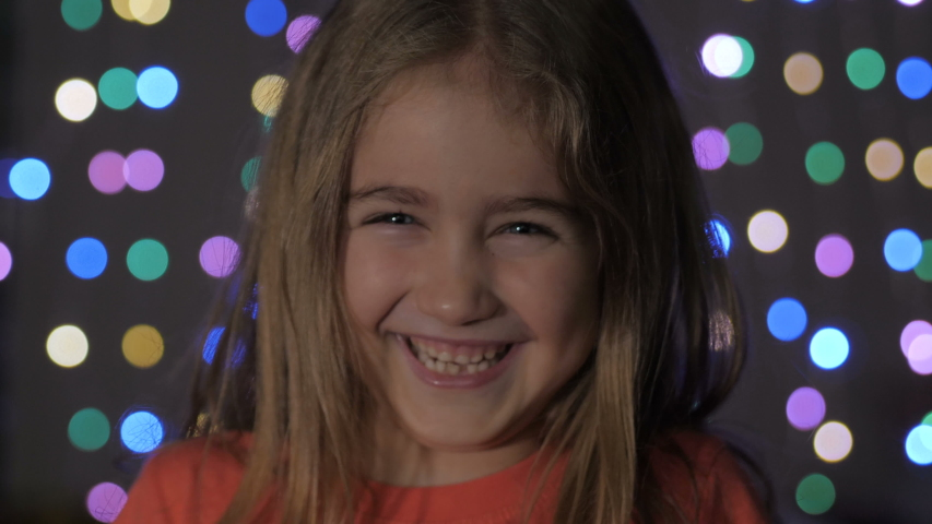 Cute Little Girl With Standing Against Glowing Christmas Lights Smiling at Camera. Portrait Child Looking at Camera. Christmas New Year Background. Lovely Girl Posing On Christmas Lights Background | Shutterstock HD Video #1041457357