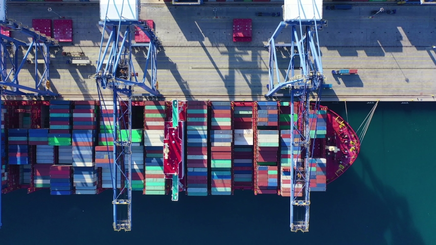 Aerial top down video of industrial cargo container logistics loading and unloading to tanker ships terminal   Shutterstock HD Video #1041501817
