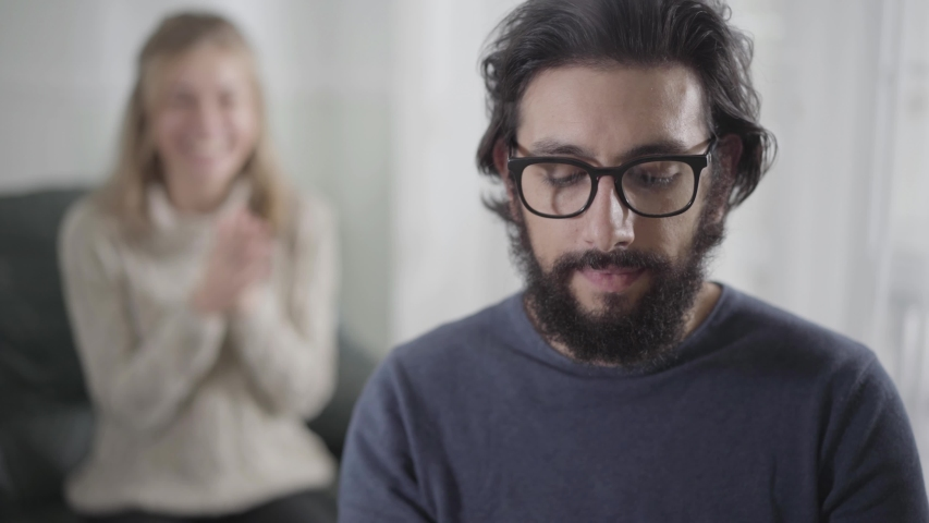 Face of shocked Caucasian man holding pregnancy test, looking back at his wife or girlfriend clapping hands, and smiling. Bearded guy in eyeglasses extremely happy to become future father. | Shutterstock HD Video #1041647827