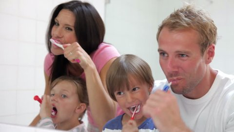 Family brushing their teeth in bathroom mirror. Shot on Canon 5d Mk2 with a frame rate of 30fps