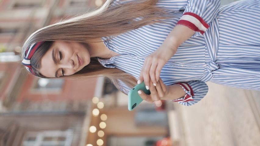 Young Attractive Girl with Brown hair and Fashionable Headband in Striped Dress Using her Smartphone Scrolling and Smiling Standing at the Street Outdoors Blurred Tramway on Background. Verlical Video   Shutterstock HD Video #1042266787