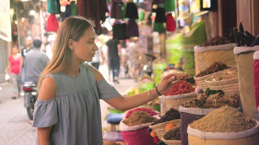 Woman walking on MAROCCAN MARRAKECH spices market. Woman walking on beautiful african arabian spices market and choose spices, travel tourist rose | Shutterstock HD Video #1042286887