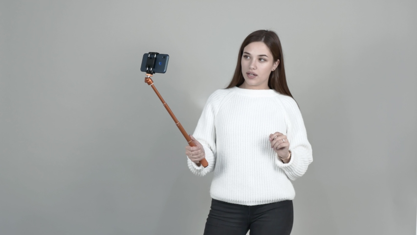 On a Gray background, Caucasian girl blogger white cardigan black jeans long straight hair brown-haired woman holding a cellphone speaks, shows her jumper, gestures, communicates with subscribers | Shutterstock HD Video #1042480957