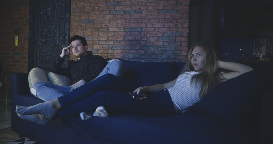 Bored couple watching tv at home. Family, relationship, marriage, love concept. Filmed on RED 4k, 12 bit color space. | Shutterstock HD Video #1042530157
