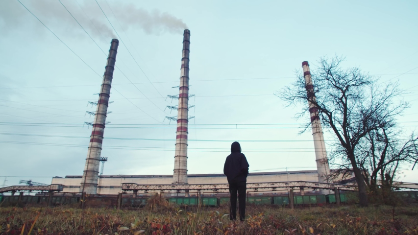 Back view of young woman in black suit standing outdoor with factory air pollution on background. Global warming concept. Industrial business. Society future. Hazardous waste treatment. Green peace. | Shutterstock HD Video #1042593457