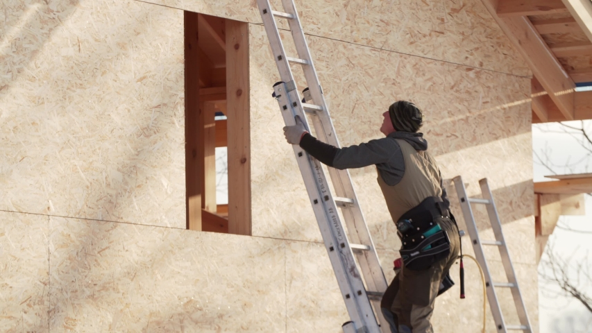 Professional builder is climbing high steel ladder with hydraulic hammer in hand. Frame residential house under construction | Shutterstock HD Video #1042593727