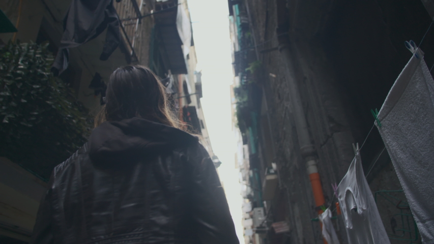 Brown haired girl walks between tall decrepit buildings in an unlit alleyway in Europe. Young woman in her thirties walking alone in an old neighborhood alleyway. Slow-motion, back view, side view. | Shutterstock HD Video #1042645327