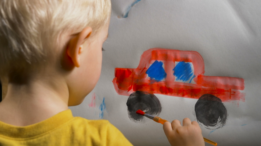 Little boy (preschooler) is painting a red toy truck with acrylic paint. Indoor kids activities, daycare, classroom. Early education concept, child creativity and art | Shutterstock HD Video #1042655647